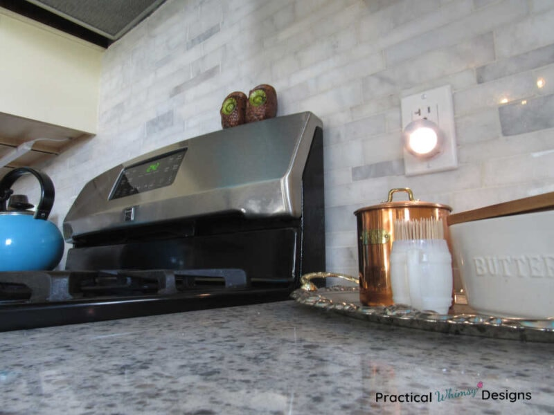 Gas stove with owl salt and pepper shakers with white marbled backsplash