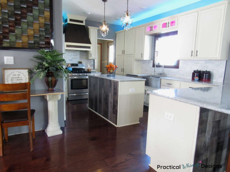 Full kitchen reveal with white cabinets, wood flooring, tile backsplash, and white quartz counters