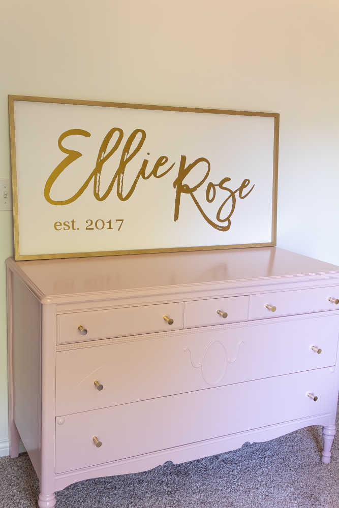 Pink painted dresser with sign on top.