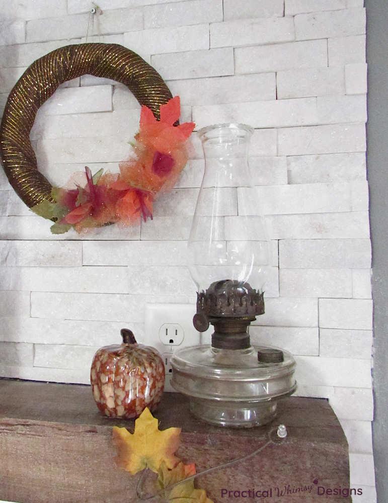Fall wreath, pumpkin, and glass oil lamp on mantel.