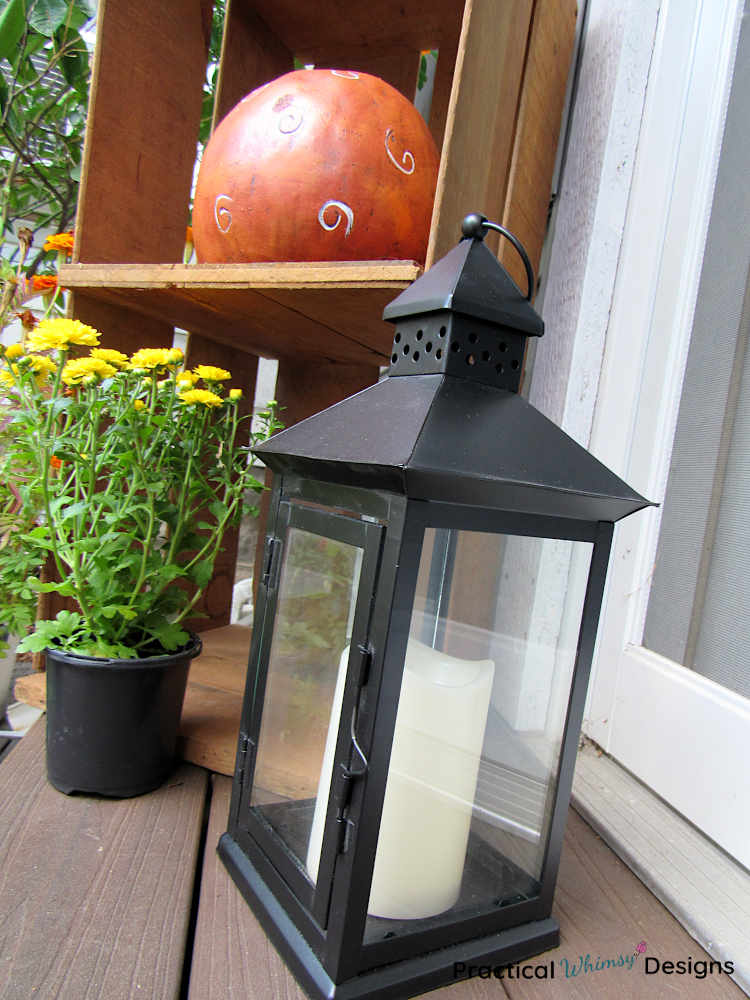 Lantern and pumpkin as small porch fall decor.