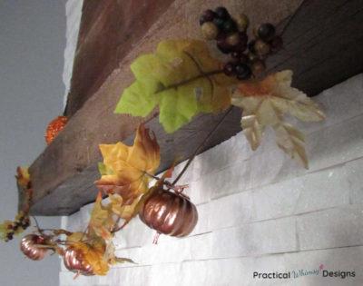 Fall pumpkin and leaf garland on mantel