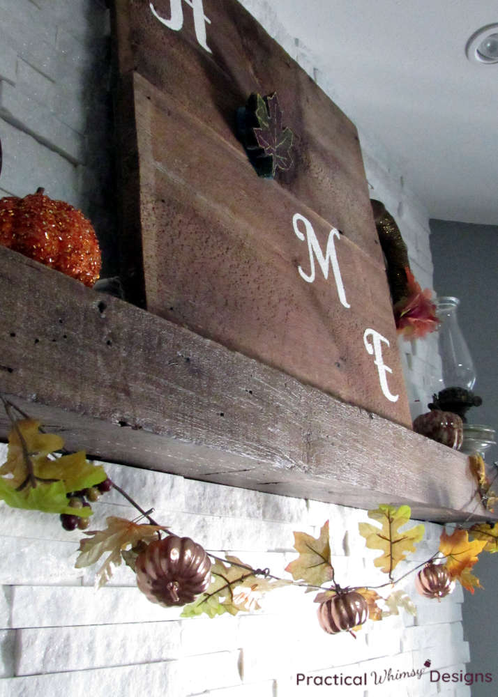 Rustic home sign with pumpkins and leaf garland on mantel.