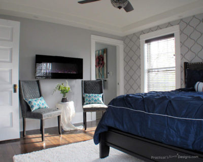 Master bedroom with gray stenciled wall, electric fireplace and gray chairs