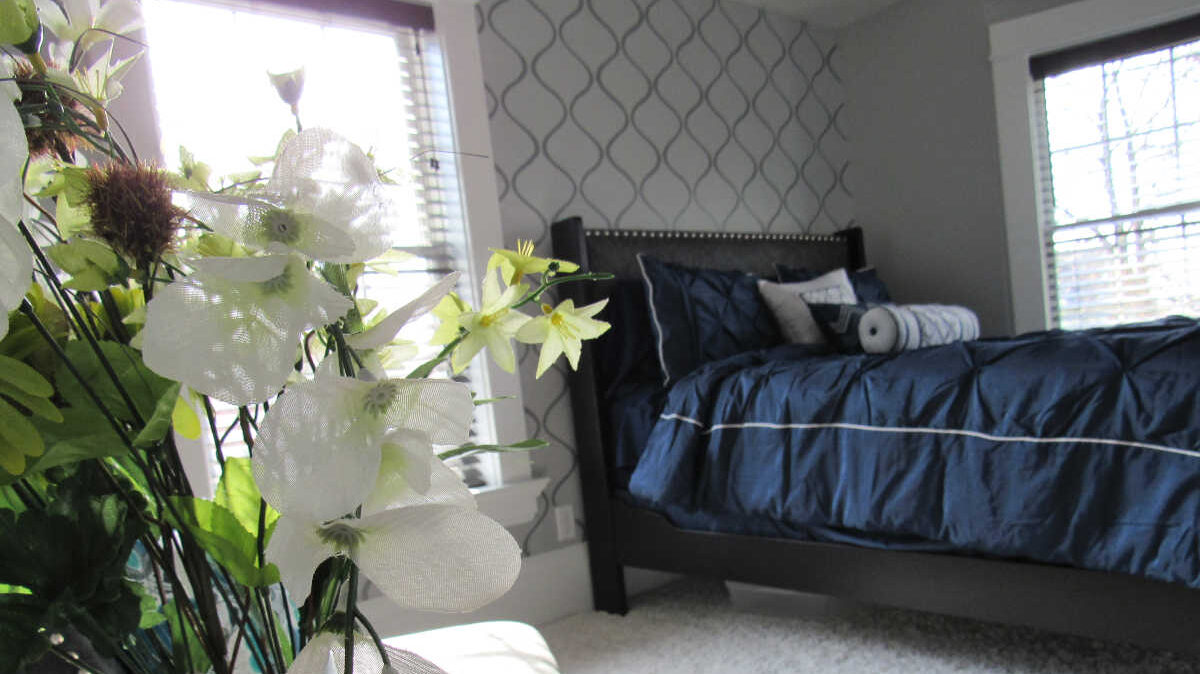 Master bedroom reveal with navy bed and gray stenciled wall