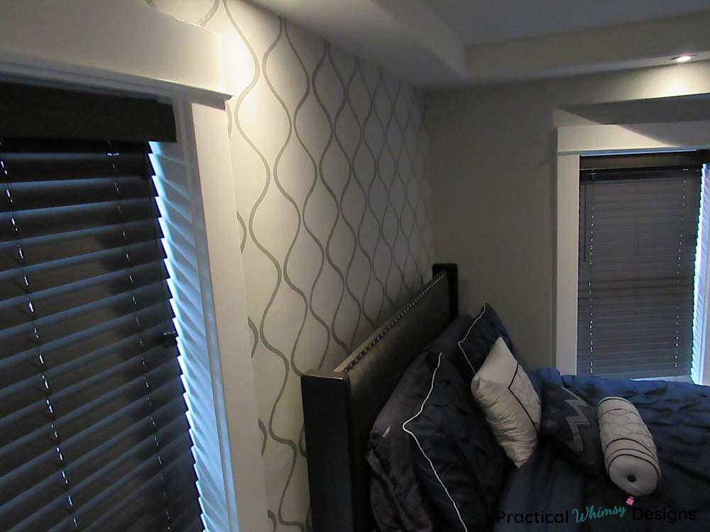 Master bedroom stenciled accent wall with master bed and windows.