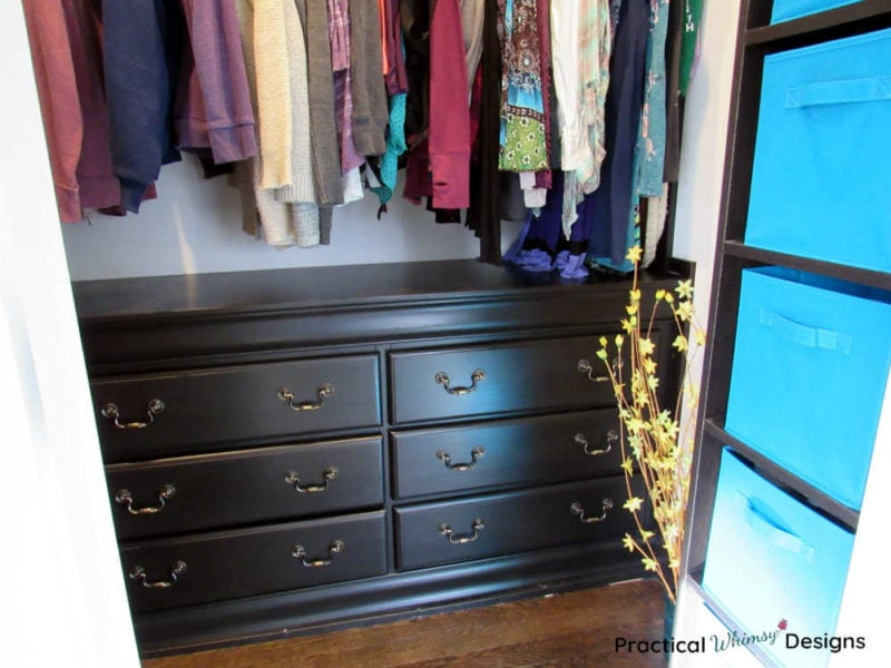 Master closet with hanging clothes and dresser