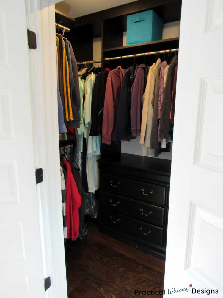 Master closet with clothes hanging in it