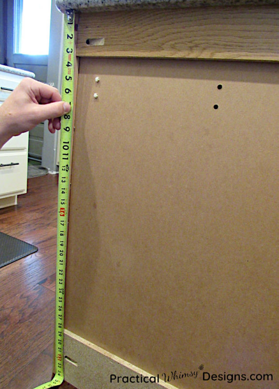 Measuring kitchen cabinet with tape measure