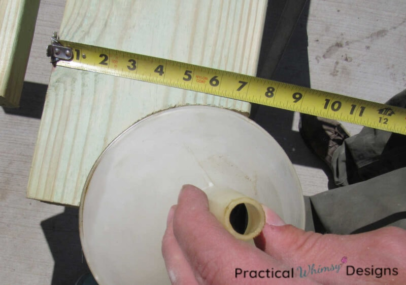 Measuring wood pergola beam arch using a funnel to outline the curve.