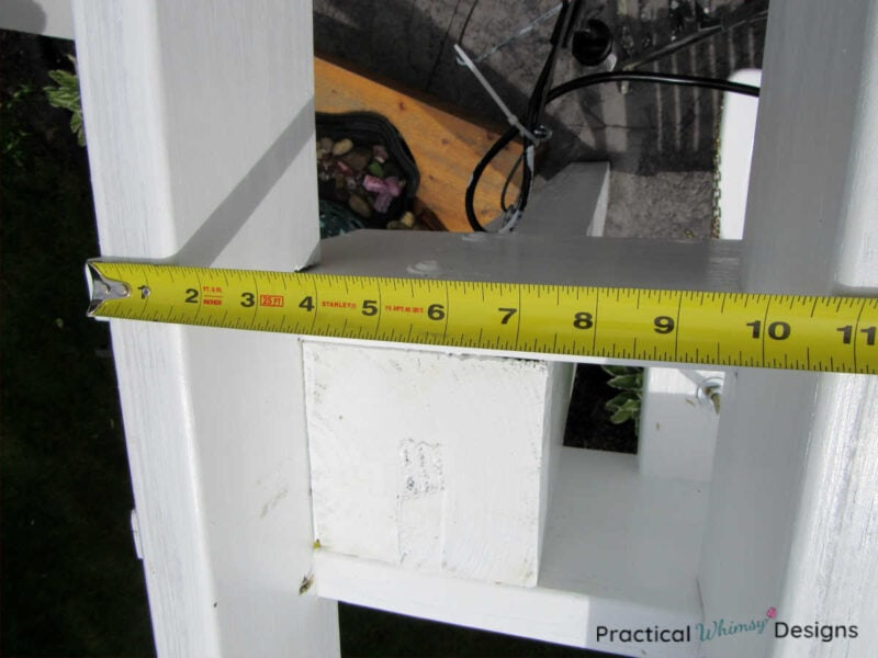 Measuring between the two pergola rafters.