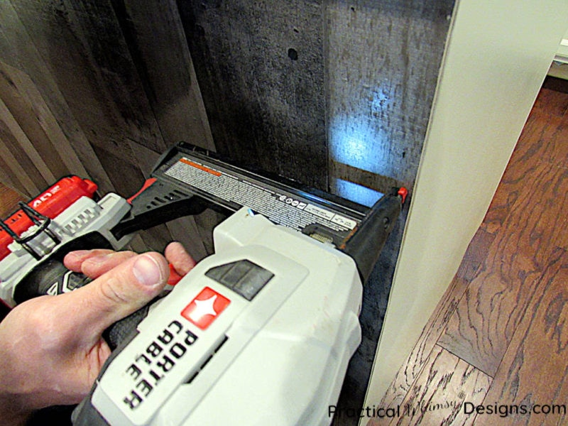 Using a trim nailer to nail paneling on cabinet