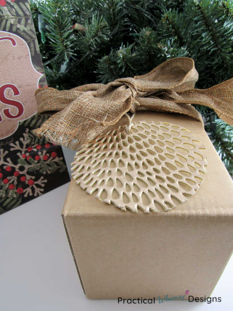 Round ornament gift tag on Christmas gift.