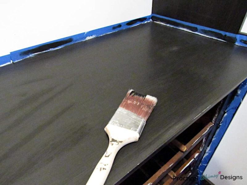 Paint brush sitting on painted dresser.