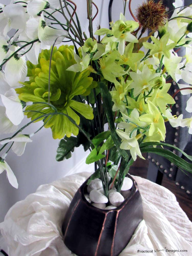 Ceramic vase painted like oil rubbed bronze with green and white flowers in it.