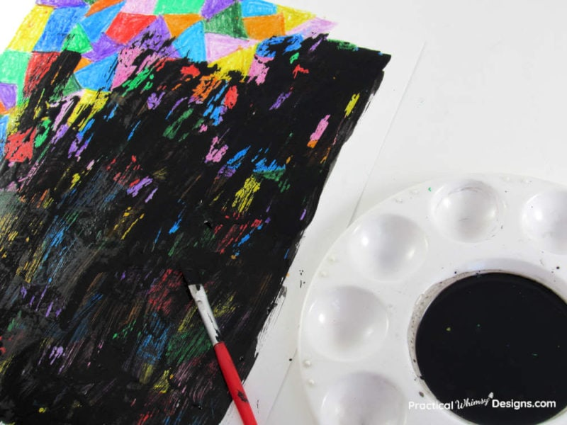 Painting acrylic black paint over crayon