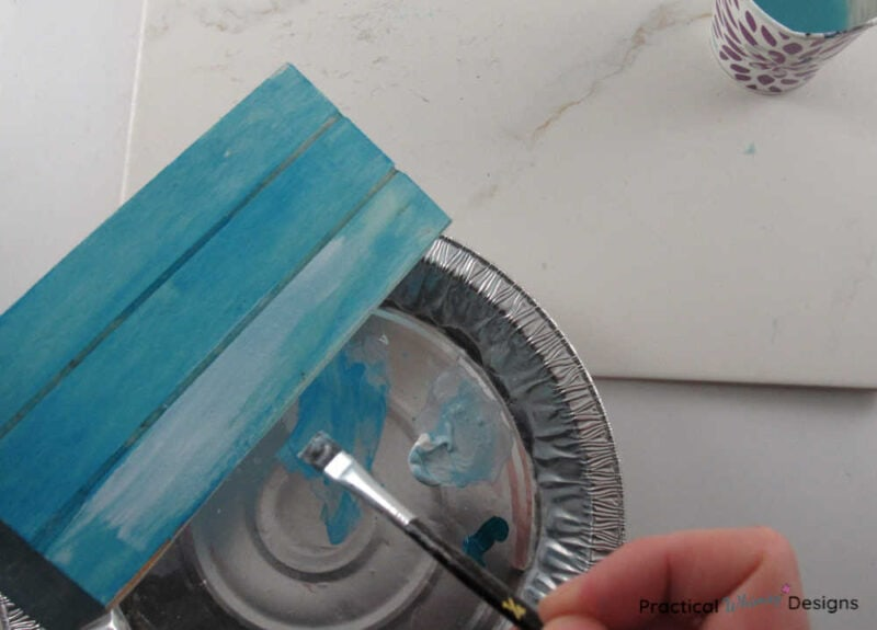 Painting white paint over blue on wooden box to create a white washed look