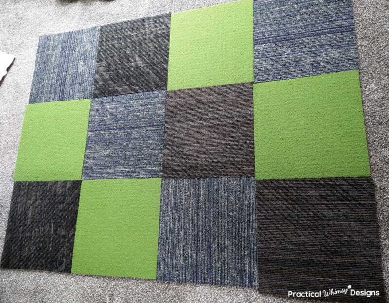 Green, black, and blue carpet squares laid out on the floor