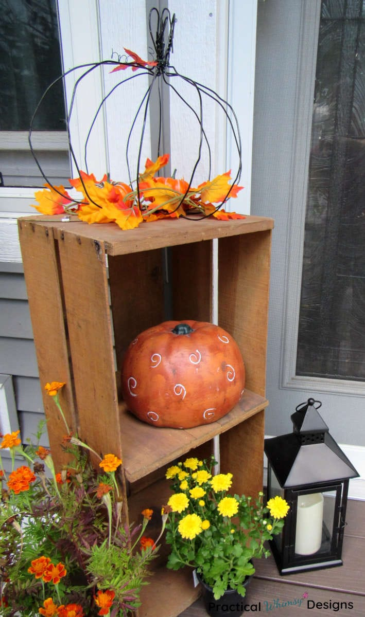 Fall pumpkins and flowers on crate