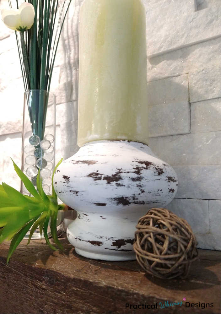 Farmhouse candlestick on mantel with onion grass flower in vase.
