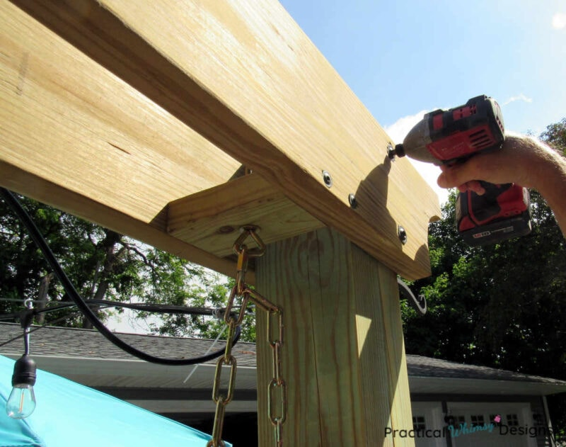 Screwing spax screws into beam to add extra support.