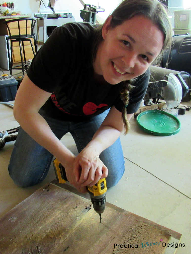 Lady smiling as she screws boards together to make a wooden home sign.