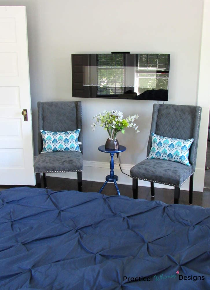 Side table in master bedroom between two chairs.