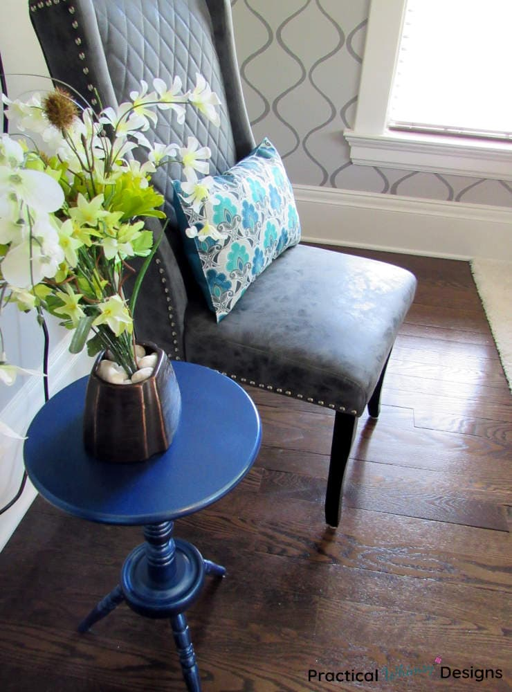Blue spray painted side table makeover with flowers and vase next to chair.