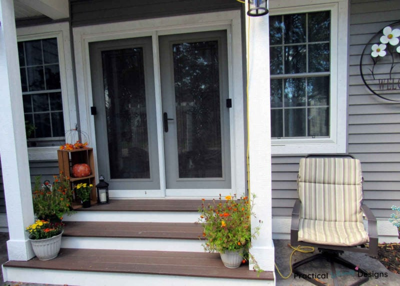 Small porch with fall decor of pumpkins and flowers