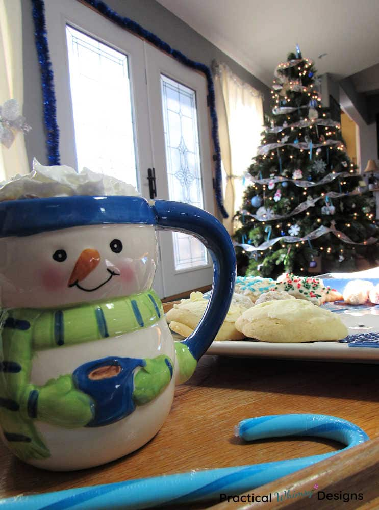 Snowman mug, blue candy cane, cookies, and winter wonderland Christmas tree.
