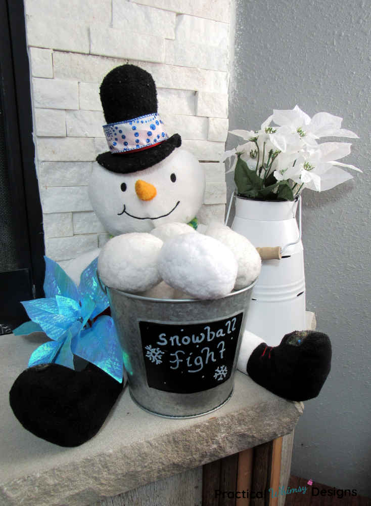 Snowman, snowballs and flowers on hearth.