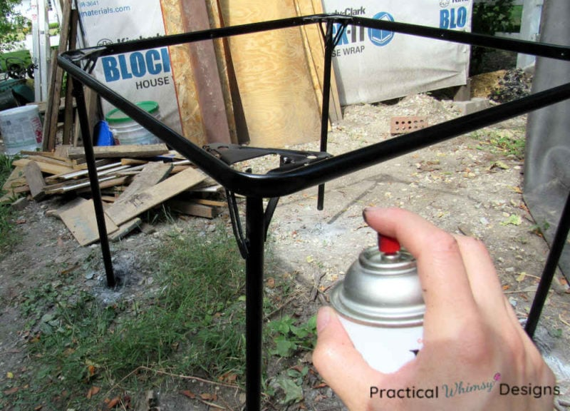 Spraying table frame with black spray paint