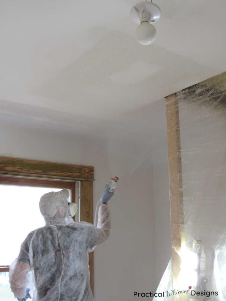 Man in paint suit spraying paint on ceilings in bedroom.