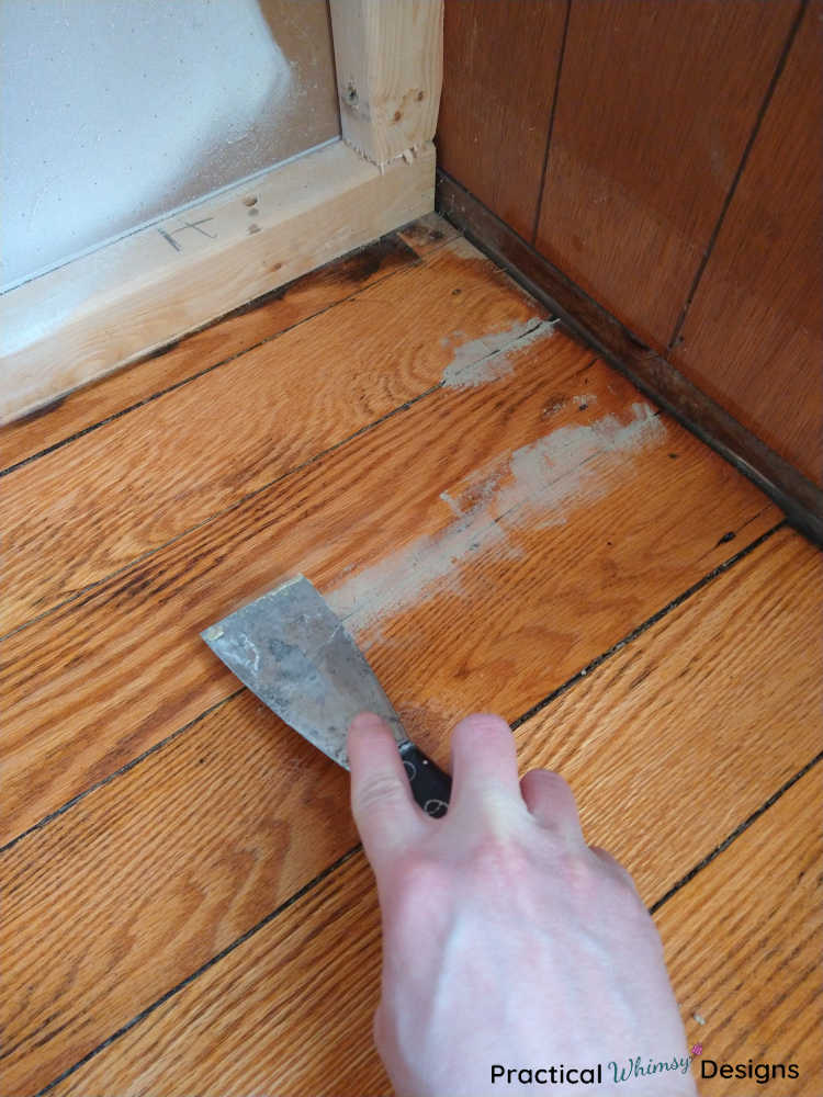 Working wood filler into gaps in the hardwood floors with a putty knife.