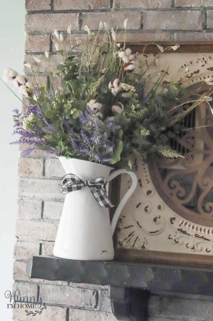 White pitcher with checkered ribbon filled with flowers sitting on a mantel.
