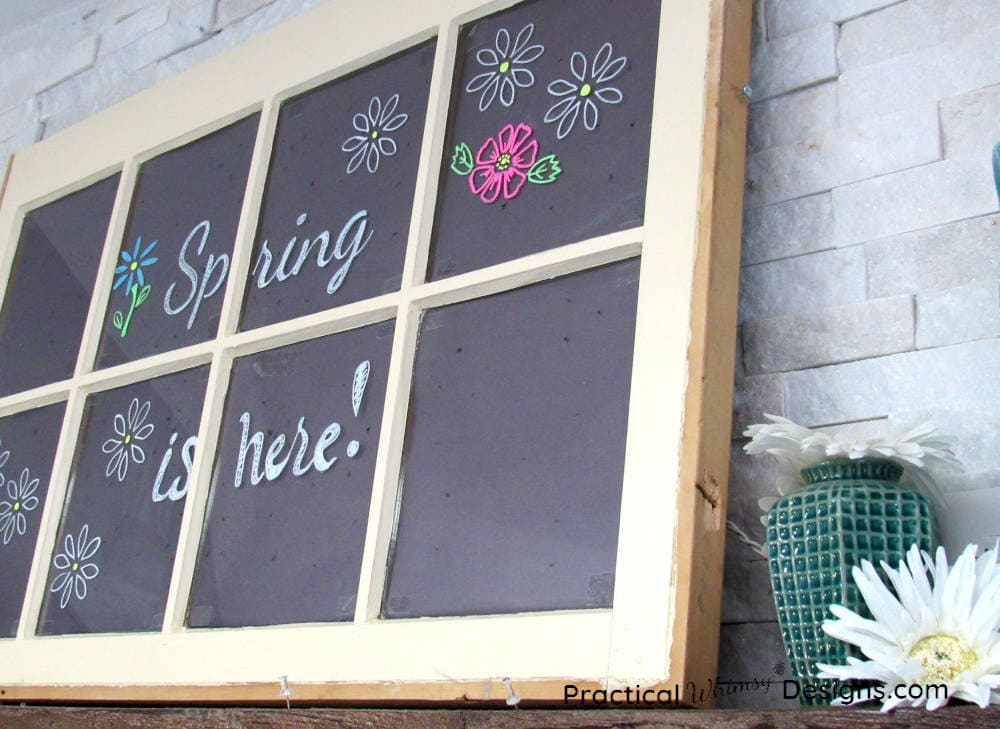 faux chalkboard spring is here and flowers stenciled on window.