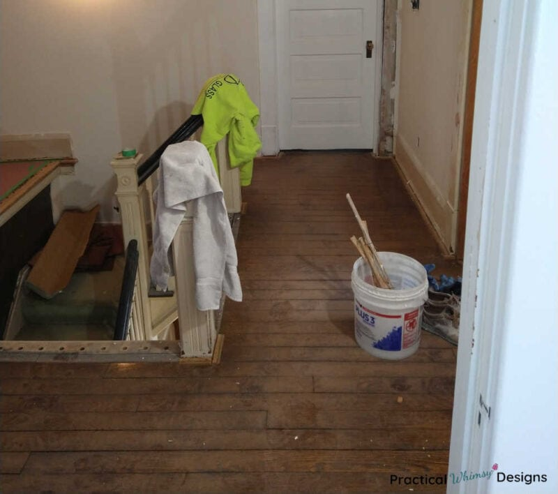 Stairs landing with unfinished hardwood floor