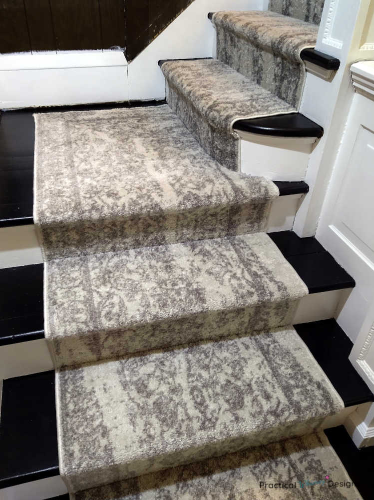 White and grey stair runner on bottom stairs.