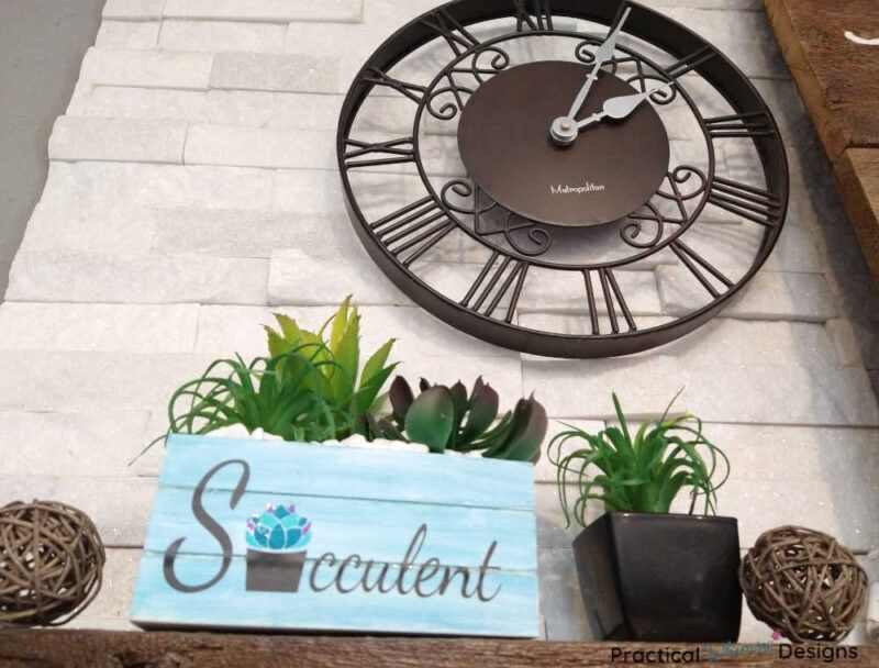 Succulent box planter with clock on mantel.