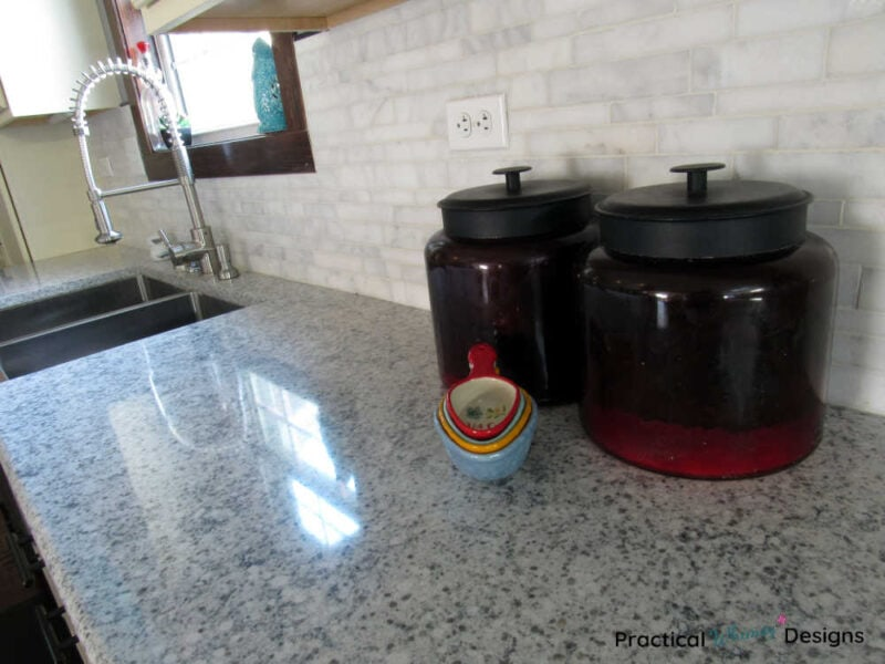 Red flour and sugar canisters on quartz counter in kitchen reveal