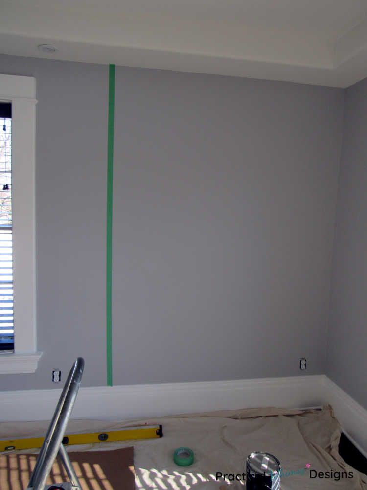 Vertical green painter's tape line on wall to help measure start of stencil.