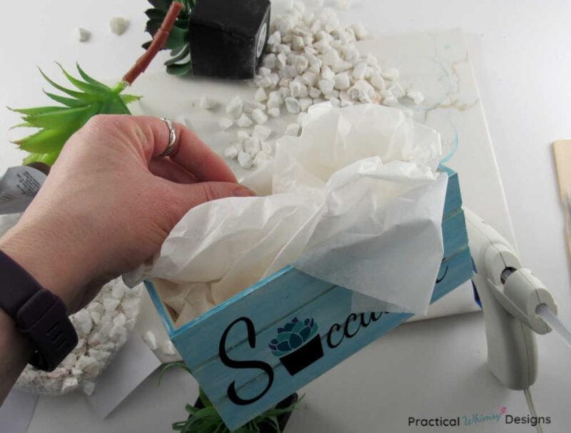Stuffing white tissue paper in bottom of succulent planter box