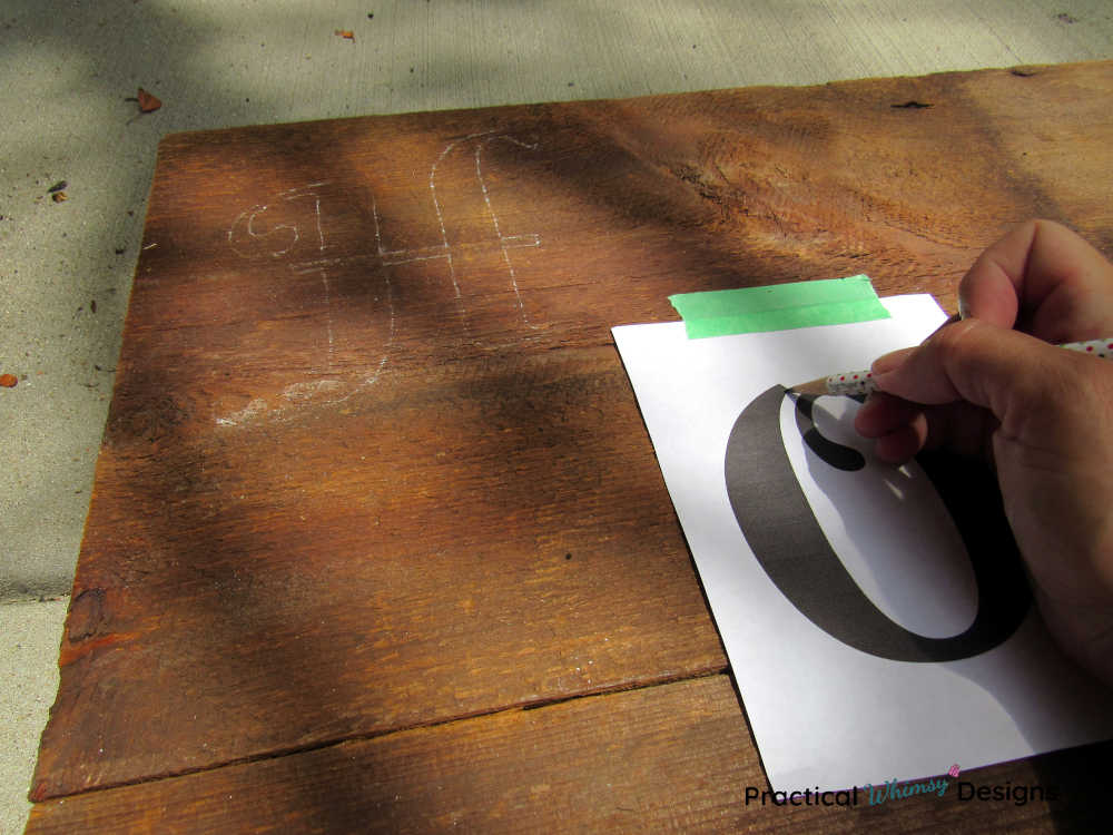 Hand tracing letters onto a wooden sign.