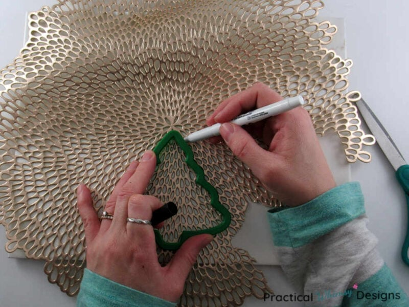 Tracing tree ornament onto gold placemat.