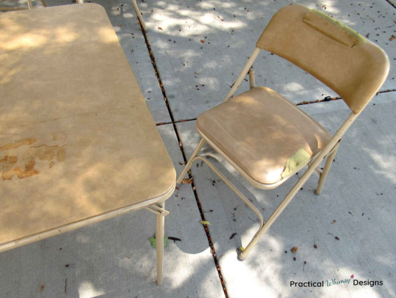 Old folding table and chair with cracked and stained vinyl