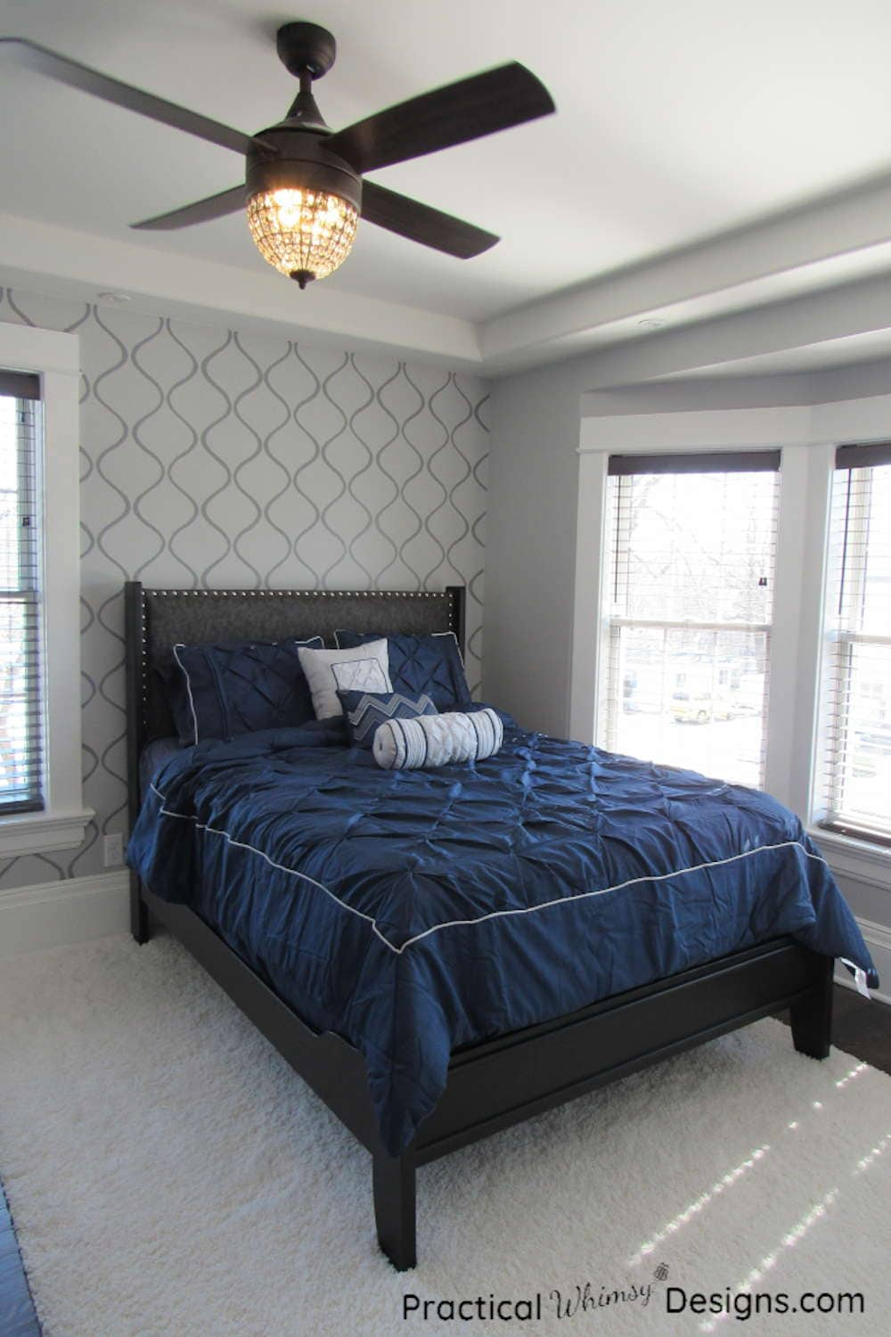 Master bed with navy comforter and gray stenciled accent wall in master bedroom.