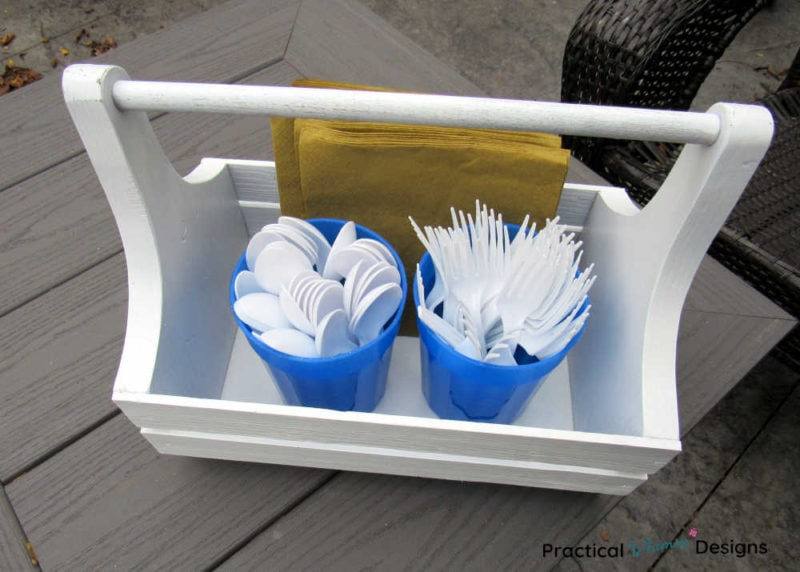 Plastic forks and spoons and napkins in a wooden caddy