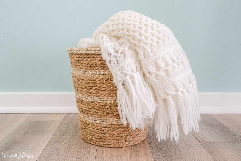 Rope basket with white blanket draped across