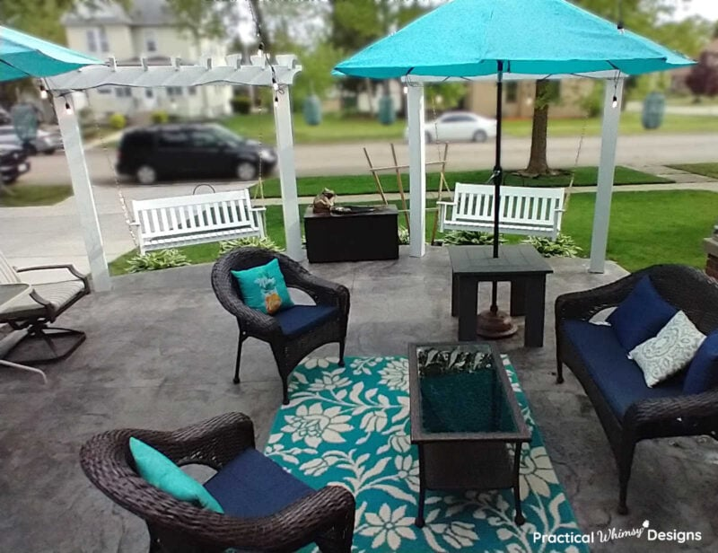 Patio with white diy wood pergolas and brown wicker furniture.