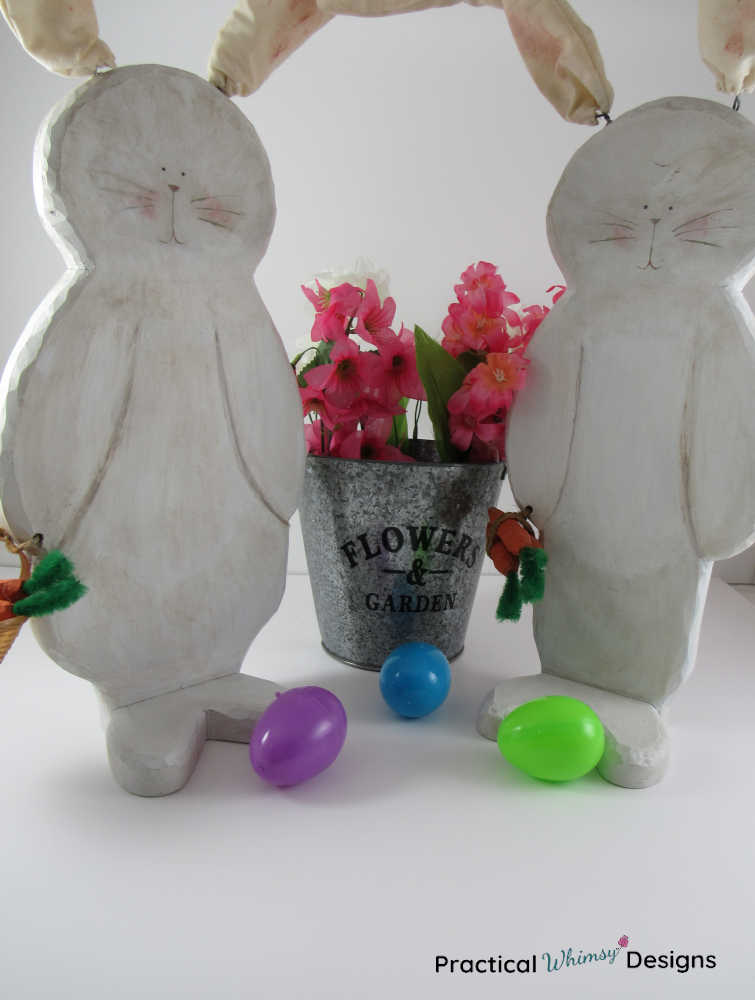 Wooden bunny decor by flowers and Easter eggs